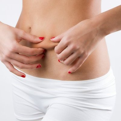 Woman showing cellulite on her belly, on white background